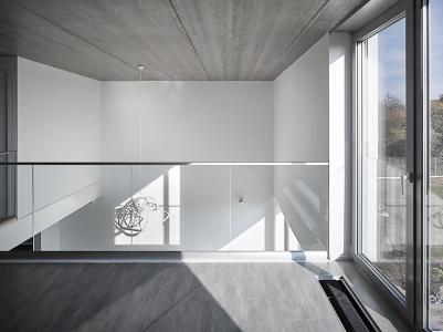 Kombinace bílé hladké omítky se světlou plechovou střechou a hliníkovými okny se propisuje i do interiéru, do světlých neutrálních odstínů podlahy a nábytku