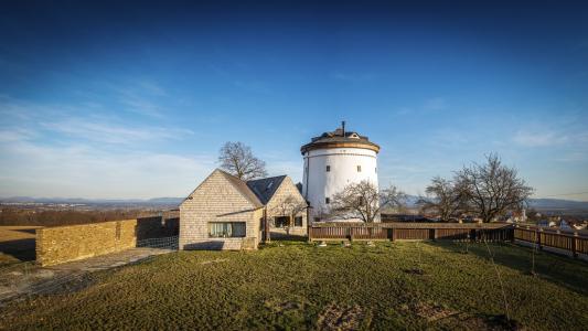 Novostavba obytného domu svou velikostí neohrožuje dominantu bílé válcové hmoty větrného mlýna. Nenarušuje ani pohledové osy, které kněmu směřují.