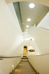 Pohled ze schodiště mezi přízemím a prvním patrem na střešní podhled se čtyřmi světlovody Lightway