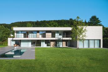 Zadní fasáda podlouhlé stavby se v obou výškových úrovních otevírá směrem do zahrady díky posuvným systémům (Schüco ASS 77 PD.SI)