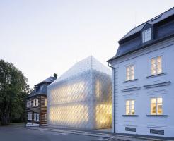 Novostavbu pokrývají na míru vyvinuté skleněné tvarovky, jež vycházejí z formátu a kladení břidlicových desek užívaných na štítech a střechách v regionu. Sklon a výška hřebene valbové střechy odpovídají typickému tvaru sousedních domů