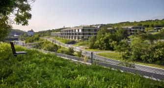 Architekti budovu navrhli tak, aby respektovala prostředí radlického údolí – kopíruje reliéf svahu, díky střešní zeleni splyne sokolím.