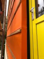 Ochrana zateplené fasády s obkladem s otevřenými spárami. Fotografie ze stavby v rozpracovaném stavu - barva jantarově oranžová (zdroj: Dörken)