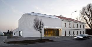 Předprostor budovy tvoří nástupní plocha dlážděná drobnou žulovou mozaikou různých odstínů, která zdůrazňuje význam budovy oproti okolní zástavbě. Fasádu nových částí domu tvoří omítka profilovaná do horizontálních říms o průřezu pravoúhlého trojúhelníku.
