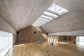 Podlaha haly a akustické obložení stěn jsou dubové, stěny z pohledového betonu. Podhled světlíků byl také akusticky upraven.