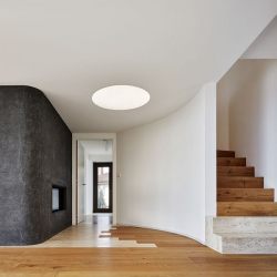 Oboustranný krb je zabudovaný do černé terrazzové stěny, z chodby se čistí a přikládá dřevo