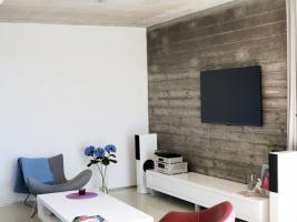 Kombinace hladkých ploch a pohledového betonu vévodí interiéru vyžadujícímu jen minimální údržbu
