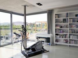 Pohledový beton je výrazným prvkem i v interiéru – například v obývací části, kuchyni a jídelně