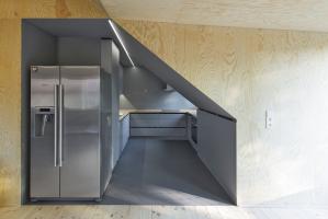 """Pohled do kuchyně: klienti už v podkroví mnohokrát zažili velmi horké letní měsíce a jejich snem byla lednice, z níž padají kostky ledu a teče dobře vychlazená voda. Stojí tedy na """"pomezí"""" mezi obývacím pokojem a kuchyní"""