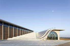 Organický tvar betonového amfiteátru vyjadřuje respekt k vinařskému řemeslu a k jeho tradici a svým elegantním reliéfem chce se svým okolím nenásilně splynout