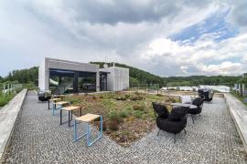 Budova nyní slouží jako administrativní a výstavní centrum, zahrada na střeše jako klidová a prezentační zóna firmy. Řešení přibližuje možnosti uplatnění zelených střech i na lehkých montovaných objektech.