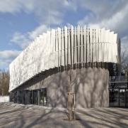 Zavěšená fasáda z hliníkových lamel tvoří kontrast k historické fasádě původního objektu