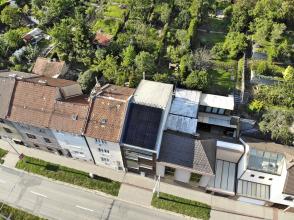 Situace: směrem do ulice domy vytvářejí souvislou uliční zástavbu, u zadních fasád na ně navazují poměrně velkorysé zahrady. Na střeše domu byly osazeny fotovoltaické panely.