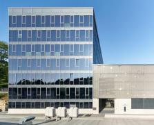 Nová výrobní hala navazuje přímo na prosklenou kancelářskou budovu. Je opatřena předsazenou textilní fasádou Schüco FACID 65. Plášť kancelářské budovy je plně prosklený ze sloupko-příčkové fasády Schüco FWS 60.HI s pevnými prvky a větracími otvíravo-sklopnými okny Schüco AWS 75 BS.HI. Integrované dvojité izolační sklo je vyrobeno z elektrochromatického skla SageGlass® od společnosti Saint-Gobain