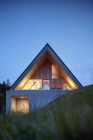 Prosklené štítové stěny propojují interiéry sokolní přírodou, zanoření podlahy zároveň poskytuje soukromí