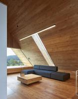 Modřín a sklo v celém interiéru, který tvoří volně plynoucí prostor s výhledy do hor
