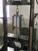 Zdvojené zkušební těleso pro zkoušku podle ČSN EN 12090:2013. Při zkoušce působí zkušební zařízení tlakem na střední kovovou plotnu. Nápad se spřažením krajních ploten závitovými tyčemi významně eliminuje nežádoucí účinky excentricity protisměrných rovnoběžných sil