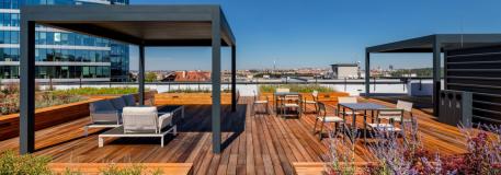 Revitalizovaná střešní terasa s posezením pod pergolou a zvýšenými záhony